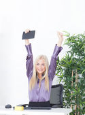 Successful young blonde businesswoman, victory gesture, hands up, smiling at office — Stock Photo