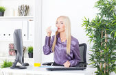 Cheerful female having a coffee break in the office — Stock Photo