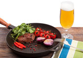 Meat, beer and vegetables in frying pan isolation — Stock Photo