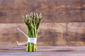 Bunches of asparagus tied on a wood background. — Stock Photo