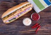 Big sandwich with fresh vegetables on wooden board — Stock Photo