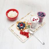 Dessert currant bilberry raspberry milk on a wooden board — Stock Photo