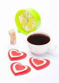 Beautiful white cup, sugar, hearts with an alarm clock on a white background — Stock Photo