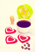 Beautiful white cup, sugar, hearts with an alarm clock on a white background. Toned in warm colors — Stock Photo