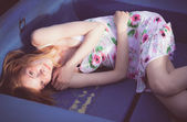 The beautiful young girl lies in the boat. toned in warm colors — Stock Photo