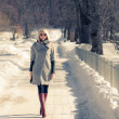 Beautiful young blond woman walking in the park in winter afternoon in coat and red boots, sunglasses. — Stock Photo #39757843