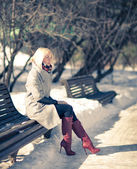 Beautiful young blond woman sitting on a bench in winter coat and red boots. Winter sunny evening. — Stock Photo