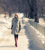 Beautiful young blond woman walking in the park in winter afternoon in coat and red boots, sunglasses. — Стоковое фото