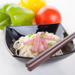 Stock Photo: Tasty noodles with ham green onions in a beautiful black bowl on a white wooden background. Pepper and tomatoes.