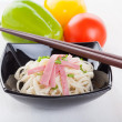 Tasty noodles with ham green onions in a beautiful black bowl on a white wooden background. Pepper and tomatoes. — Stock Photo