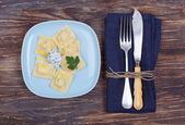 Ravioli on a blue plate with a beautiful vintage fork and a knife on a blue napkin on a dark wooden board — Stock Photo