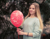 Open portrait of the young woman the beautiful woman in cold weather in park. The sensual blonde poses and is cheerful with a red balloon. — Stock Photo