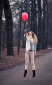 The sensual blonde poses and cheerfully jumps with a red balloon. — Stock Photo