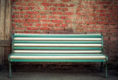 Beautiful multi-colored bench at a brick wall — 图库照片