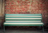 Beautiful multi-colored bench at a brick wall — Stock Photo