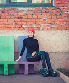 The girl in black and cool boots sits on a color bench — Foto de Stock