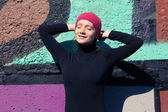 The girl in the black sunbathes at a multicolored wall in a red cap — Stock Photo