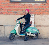 The girl in the black sits on the vintage green scooter with vintage the camera — 图库照片