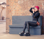 The girl in black clothes photographs the vintage camera sitting on a gray bench — Stock Photo