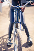 The girl in black clothes the cool bicycle with the vintage camera in a cover a sunlight — Stock Photo