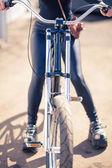 Dívka v černém oblečení cool kolo s vinobraní fotoaparát v přebalu a slunečního záření — Stock fotografie