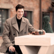 The young man model in a coat sits at a white table with the vintage camera outdoors — Stock Photo #45563777