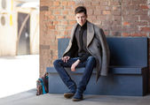 The young man poses in a coat sitting on a bench — Stock Photo