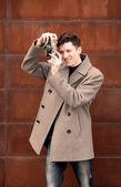Il giovane in una fotografie cappotto modello la macchina fotografica d'epoca a un muro di metallo arrugginito — Foto Stock