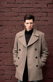The young man model in a coat poses at a brick wall. Toned — Stock Photo