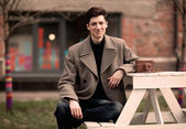 The young man model in a coat sits at a white table with the vintage camera outdoors — Stock Photo