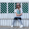 The Beautiful Young Girl with Long Hair in Sunglasses sits at white wooden Steps in the Summer. — Stock Photo