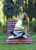 The beautiful girl fitness sit in a wooden chair. Short top sports pants. — Stock Photo