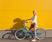 Young sexy blonde girl is standing near the vintage green bicycle with brown vintage bag — Stock Photo