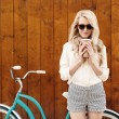 Young sexy blonde girl with long hair in sunglasses standing near vintage green bicycle and holding a cup of coffee have fun and good mood looking in camera and smiling, warm, tonning — Stock Photo #51047439