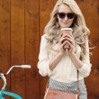 Young sexy blonde girl with long hair with brown vintage bag in sunglasses standing near vintage green bicycle and holding a cup of coffee, have fun and good mood looking in camera and smiling, warm, — Stock Photo #51047443