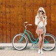 Young sexy blonde girl with long hair with brown vintage bag in sunglasses standing near vintage green bicycle and holding a cup of coffee, have fun and good mood looking in camera and smiling, warm, — Stock Photo #51047447