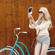 Young sexy blond woman standing near a green vintage bicycle holding photos and smiling, warm, tonning — Stock Photo #51047449