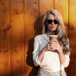 Young sexy blonde girl with long hair in sunglasses holding a cup of coffee have fun and good mood looking in camera and smiling evening soft sunlight, warm, tonning — Stock Photo #51047453