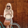 Young sexy blonde girl with long hair with brown vintage bag in sunglasses standing near vintage green bicycle and holding a cup of coffee, have fun and good mood looking in camera and smiling, warm, — Stock Photo #51047479