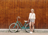 Young sexy blonde girl with long hair standing near vintage green bicycle have fun and good mood looking in camera and smiling, warm, tonning — Stockfoto