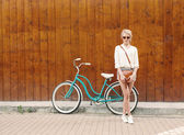 Young sexy blonde girl is standing near the vintage green bicycle with brown vintage bag in orange sunglasses, warm, tonning — Stock Photo