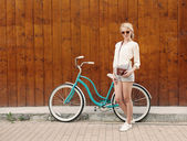 Young sexy blonde girl is standing near the vintage green bicycle with brown vintage Cameras in orange sunglasses., warm, tonning — Stock Photo