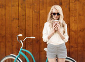 Young sexy blonde girl with long hair in sunglasses standing near vintage green bicycle and holding a cup of coffee have fun and good mood looking in camera and smiling, warm, tonning — Stock Photo