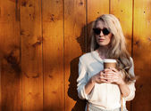 Young sexy blonde girl with long hair in sunglasses holding a cup of coffee have fun evening soft sunlight, warm, tonning — Stock Photo