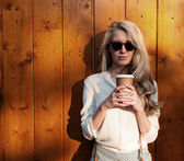 Young sexy blonde girl with long hair in sunglasses holding a cup of coffee have fun and good mood looking in camera and smiling evening soft sunlight, warm, tonning — Stock Photo
