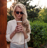 Young sexy blonde girl with long hair in sunglasses holding a cup of coffee have fun and good mood looking in camera and smiling, warm, tonning — Stockfoto