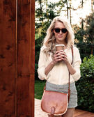 Young sexy blonde girl with long hair in sunglasses with brown vintage bag holding a cup of coffee have fun and good mood looking in camera and smiling, warm, tonning — Stockfoto