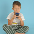 Stock Photo: Young boy playing handheld game console