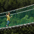 A young boy walks on a suspension bridge - Stok fotoğraf