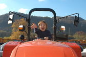 Boy driving a tractor — Stock Photo